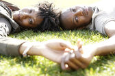 Close up portrait of a young african american couple laying down on green grass in the city — Stock Photo