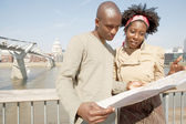 Black couple looking at a guide map on vacation — Stockfoto