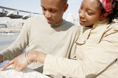 Attractive black couple pointing at a guide map on vacation — Stock Photo