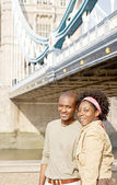 Attractive african american couple walking passed Tower Bridge in London — Stock Photo