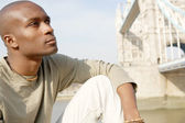 Attractive african american man sitting by Tower Bridge in London — Stock Photo