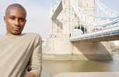 Attractive african american man standing by Tower Bridge in London — Stock Photo