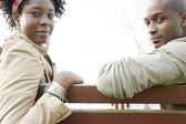 Young couple sitting on a wooden bench — Stock Photo
