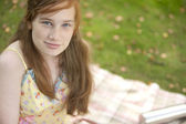 Red hair teenager smiling at camera while sitting on a blanket in the forest. — Stock Photo