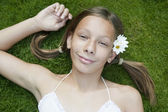 Portrait of teenage girl laying down on grass. — Stock Photo