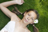Tonårig flicka fastställande på grönt gräs, titta på kameran. — Stockfoto