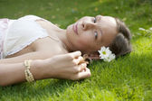 Side view of teenage girl laying down on grass. — Stock Photo
