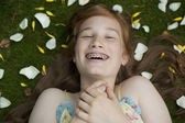 Overhead view of teenage girl with flower petals, laughing and wearing braces. — Stock Photo