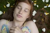 开销近距离少女睡在草,包围的花瓣上的视图. — 图库照片