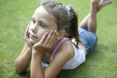 Child laying down on grass, thoughtful. — Stock fotografie