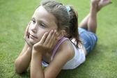 Niño se establecen sobre hierba, pensativo. — Foto de Stock