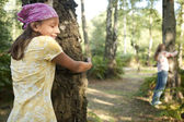 Teenage girls hugging trees in the forest. — Stock Photo