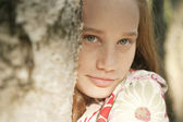 Teenage girl looking at camera through a tree trunk. — Stock Photo
