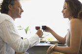 Mature couple toasting with red wine while having lunch in a hotel. — Stock Photo