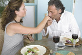 Mature man kissing woman's hand while having a healthy luch at home. — Stock Photo