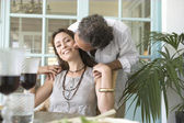 Mature man kissing woman while having a healthy lunch at home. — Stock Photo