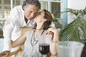 Mature woman kissing man while having a red wine drink at home. — Stock Photo