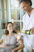 Mature man pouring champagne into flute glasses with partner at home. — Stock Photo