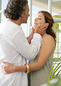 Close up of a mature couple hugging in a home terrace with large french doors. — Stock Photo