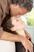 Close up view of a mature man kissing woman's forehead while lounging at home's living room. — Stock Photo