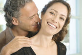 Mature man and woman hugging and whispering in each other's ear at home. — Stock Photo