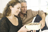 Mature man giving a woman a box of chocolates at home. — Stock Photo