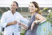 Mature couple drinking champagne while leaning on a hotel's balcony outdoors. — Stock Photo