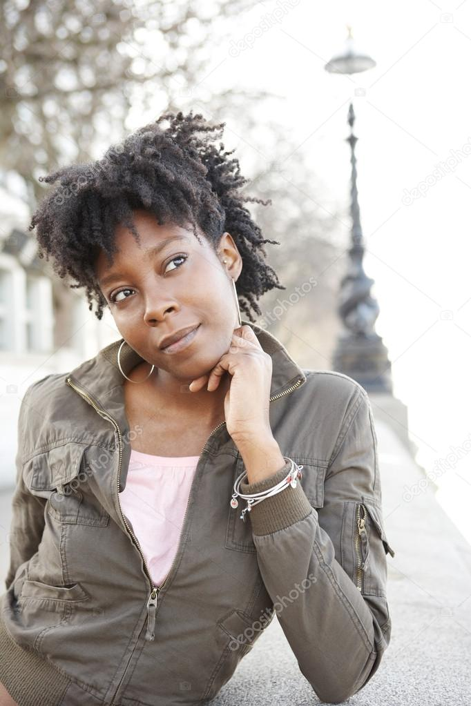 Attractive african american woman leaning on the river Thames' south bank, being thoughtful. — Stock Photo #20082561
