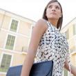 Young businesswoman walking passed classic office buildings in a city square, carrying a black folder. — Stock Photo