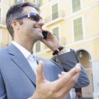Portrait of a young businessman speaking on his cell phone in the financial district. — Stock Photo