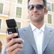 Businessman using his smart phone while standing in front of a classic office building in the city. — Stock Photo