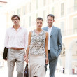 Team of three business walking together through a classic city square with office buildings in the background during a sunny day. — Stok fotoğraf