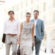 Stockfoto: Team of three business walking together through a classic city square with office buildings in the background during a sunny day.