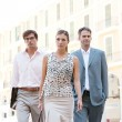 Team of three business walking together through a classic city square with office buildings in the background during a sunny day. — Foto Stock