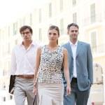 squadra di tre business camminando insieme attraverso una piazza della città classica con uffici in background durante una giornata di sole — Foto Stock