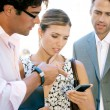 Team of three busy business gathering around in a casual meeting outdoors — ストック写真