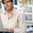 Attractive businessman wearing glasses and using a laptop computer in the city — Stock Photo