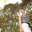 Stock Photo: Businesswoman standing high in a city park with a tree filtering the sun rays.