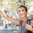 Photo: Attractive young businesswomraising her arm to call taxi in busy city, outdoors.