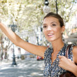 Foto de Stock  : Attractive young businesswomraising her arm to call taxi in busy city, outdoors.