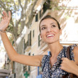 Attractive young businesswoman raising her arm to call a taxi in a busy city — Stock Photo