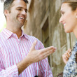 Businessman and businesswoman having an animated conversation outdoors - Stock Photo