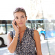 Stock Photo: Attractive commuting businesswomusing her smart phone in city near bus stop.