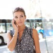 Attractive commuting businesswoman using her smart phone in the city near a bus stop. — Stock Photo #20202659