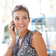 Attractive commuting businesswoman using her smart phone in the city near a bus stop. — Stock Photo