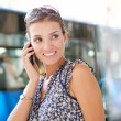 Attractive commuting businesswoman using her smart phone in the city — Stock Photo #20202681
