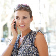 Attractive businesswoman having a conversation on her smart phone in a classic city — Stock Photo