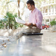Businessman reading a newspaper while sitting down on a stone step in a classic city square — Foto Stock