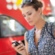 Stock Photo: Portrait of attractive commuting businesswomusing her smart phone in city near bus stop.