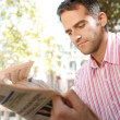 Portrait of a senior businessman reading a financial newspaper — Stock Photo